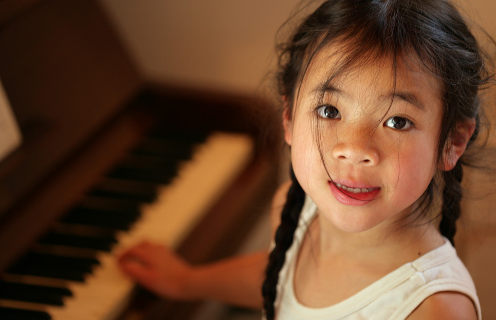 child - beginner profile looking in fthe camera while playing piano